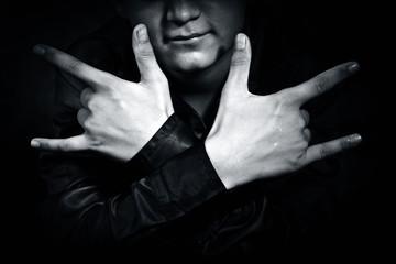 Caucasian boy with symbolic hands gesture mimicking dark art.