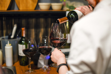 Waiter pouring wine. Skillful sommelier pouring red wine into glass. Woman holding bottle and wineglass standing in cellar
