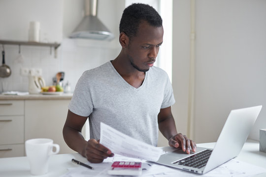 Concentrated young african american student using online banking application with hand on touchpad, looking at screen of his laptop, trying to make payment for university education. Financial problems