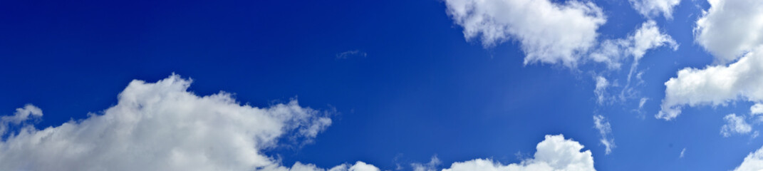 Panorama of spring, summer clouds on a blue sunny sky, background.