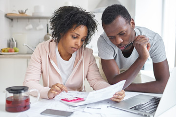 Young african american couple doing paperwork together, planning family budget, calculating domestic expenses, sitting at kitchen table with laptop and calculator at home. Financial problems concept