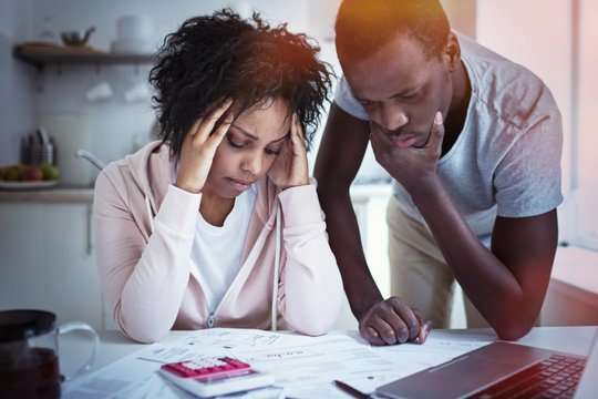 Young stressed african american couple in trouble, have no money to pay debts, to pay rent for appartment. Wife holding head in despair, can not pay bills, having financial troubles. Household budget