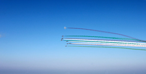 Group of airplanes with colored track red, white, green clouds on blue sky background, horizontal view. Colors of italian flag.