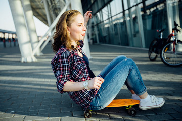 Pretty teen girl sitting and rolling on skateboard