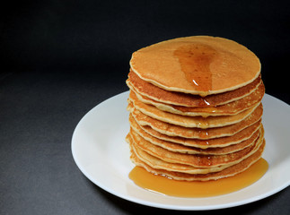 Stack of Fresh Homemade Pancakes with Maple Syrup, Served on White Plate, Black Background