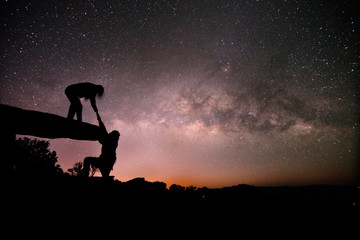 Couple pull each other on Stone lodge under night sky stars with milky way background