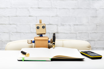Robot sits at the table and writes a pen in his notebook