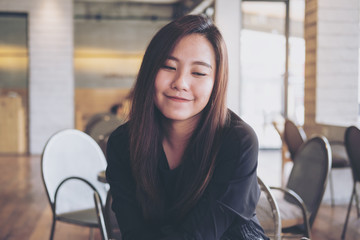 A beautiful Asian woman sitting in modern cafe with smiley face and feeling happy