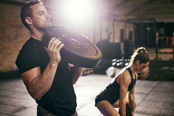 Young sportsmen having workout with weight disks Wall mural
