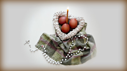 Easter composition on the table. Colored eggs in a white wicker heart with a burning candle and a cross.