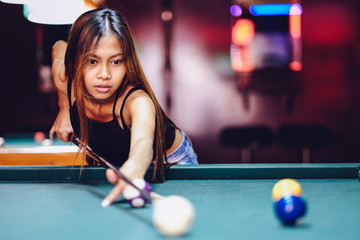 Young beautiful girl playing billiard in a club