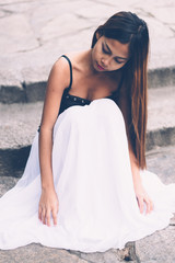 Young beautiful girl in white long dress siting on the concrete floor