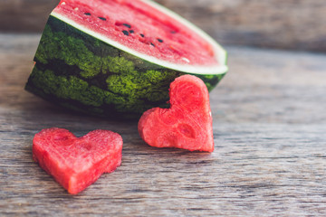 Healthy watermelon smoothie with mint, a piece of watermelon, hearts and a striped straw on a wood background
