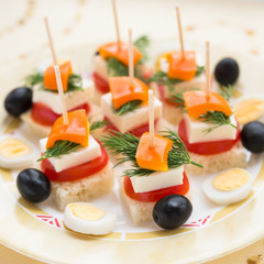Cold snacks. Canapes of feta cheese and vegetables