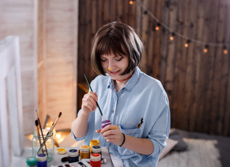 Young woman painter holding brush, smiling and painting a picture