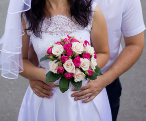 Bride and groom holding wedding bouquet with roses