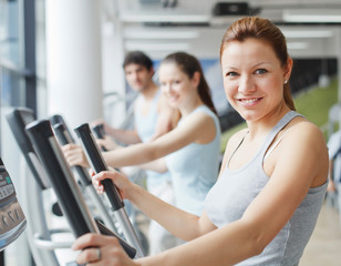 People exercising on cardio machines in the gym.