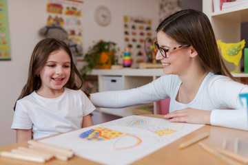 Smiling mother and daughter enjoying quality time together learning