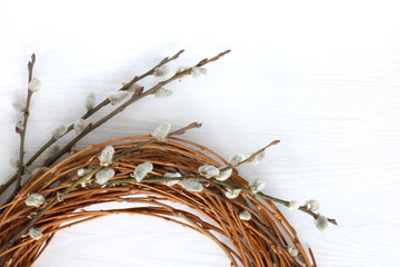 festive decoration/ Wreath of twigs with willow branches on a light wooden surface