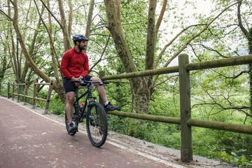 chico moreno con barba practicando ciclismo en la naturaleza con su bicicleta