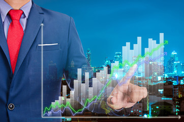 businessman point on virtual graph on screen with night modern city building background