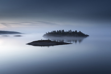 The island is in a fog. Karelia. Fog on the water.