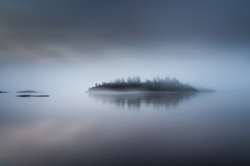 The island is in a fog. Karelia. Fog on the water.