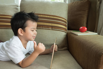 Asian boy in the living room on the couch playing tablet.