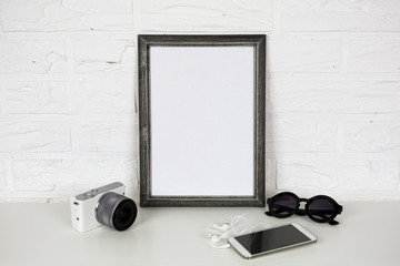 Frame White Mock Up and Modern Accessories. on Brick Wall Background. Mirrorless Photo Camera, Mobile Phone with Headphones and Glasses. Trendy Template Mockup in Black, White and Gray Colors.