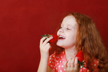 Funny little girl is eating strawberry