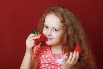 Funny little girl is eating tasty strawberry, on red background.
