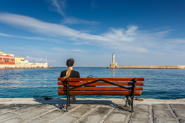 Girl sitting on bench and looking at sea.