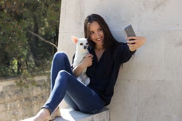 girl and chihuahua dog taking selfie