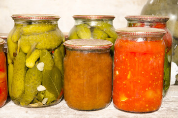 Dusty glass jars with canned fruits and vegetables in storage.