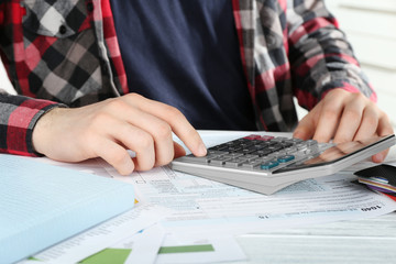 Man sitting at table with calculator and documents