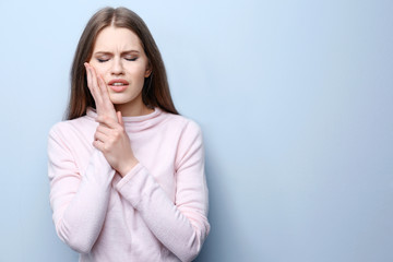 Young woman suffering from toothache on light background