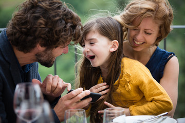 Family laughing with smartphone outdoors