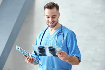 Young medical assistant with x-ray image and clipboard in clinic