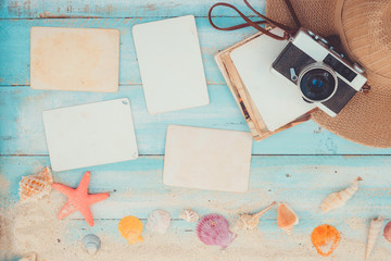 Top view composition - Blank paper photo frames with starfish, shells, coral and items on wooden table. Concept of remembrance and nostalgia in summer tourism, travel and vacation. vintage color tone.