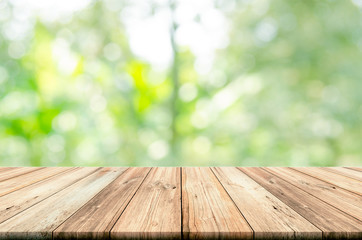 Empty wooden table top with blurred natural abstract background.