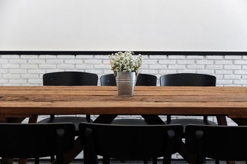 Empty cafe seating area with wooden table and chairs in minimal style