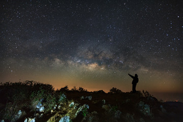 A Man is standing next to the milky way galaxy pointing on a bright star at Doi Luang Chiang Dao with Thai Language top point signs. Long exposure photograph.With grain