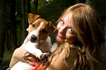 Portrait of young and attractive woman with long hair with her lovely dog sitting in the park. Trees on background. Looking at camera.