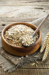 Oatmeal in the wooden plate on wooden background. Healthy Breakfast.