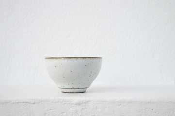white ceramic tea cup with cement wall background