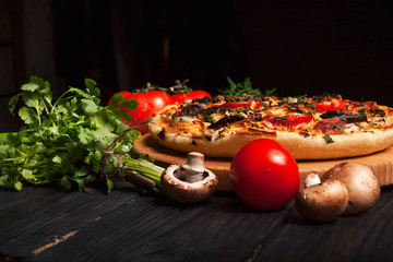 Fresh tasty pizza on black background on rustic wooden table with ingredients. Italian food.