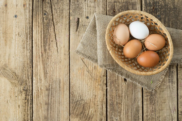 Eggs of different colors on wooden background