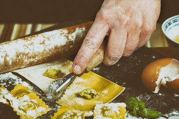 Hand of a woman working with the cutter and the stuffing to make ravioli, italian stuffed pasta.