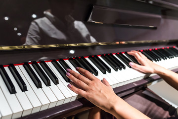 Young woman hands playing on piano (shallow DOF)