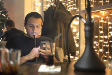 man smoking pipe of hookah in night cafe